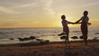 Girl and Man Having Fun Together on the Beach. Holding Hands and Whirling in Sunset Time.
