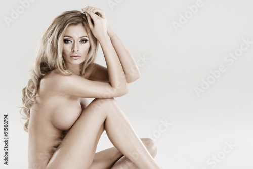 Beautiful young naked blonde woman sitting over the background Canvas Print