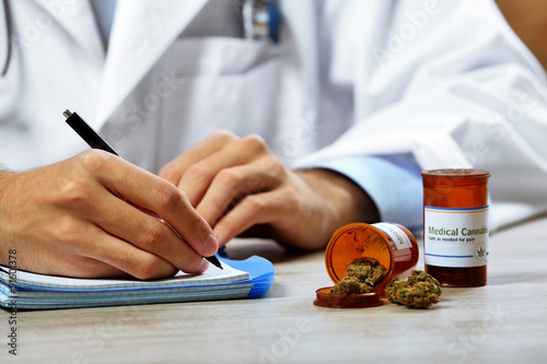 Photo  Doctor writing on prescription blank and bottle with medical cannabis on table c