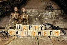 Happy Halloween Wooden Blocks With Spiders, Skeletons And Old Wood Background