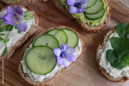 Fotografie, Obraz  Green sourdough open face sandwiches with purple edible flowers