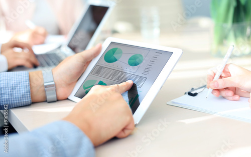 Obraz Business person analyzing financial statistics displayed on the tablet screen - fototapety do salonu