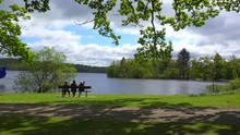 People Sit On A Bench Enjoying The Scenery At Loch Lomand Scotland.