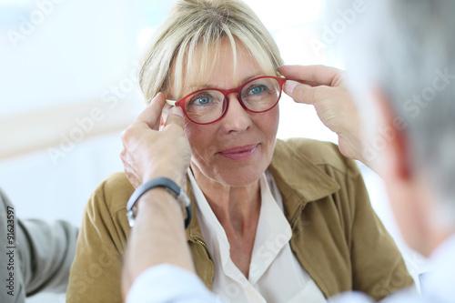 Fotografía  Senior woman trying new eyeglasses on, optical store