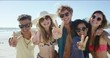 Group of friends smiling and making peace sign at camera for a portrait on the beach