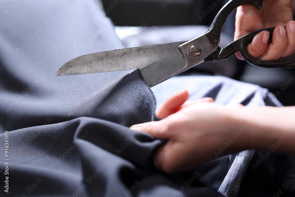 Fototapeta Krawiec.Dłonie krawca wycinającego tkaninę nożyczkami krawieckimi
