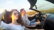 Young Caucasian couple fun driving luxury cabriolet convertable car. SLOW MOTION stock footage