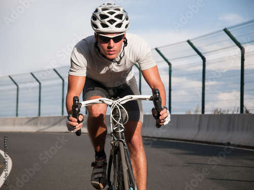Cyclist portrait in action on the road Canvas Print