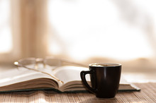 Cup Of Coffee Glasses Rest On The Open Book Against The Window I