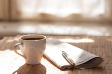 Cup Of Black Coffee, Newspaper And A Pen Against The Window In T