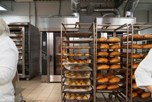 Racks Of Fresh Loaves Of Bread And Buns From Ovens In Bakery