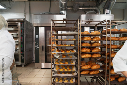 Foto op Aluminium Bakkerij Racks of fresh loaves of bread and buns from ovens in Bakery