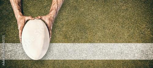 Obraz na plátně Composite image of man holding rugby ball