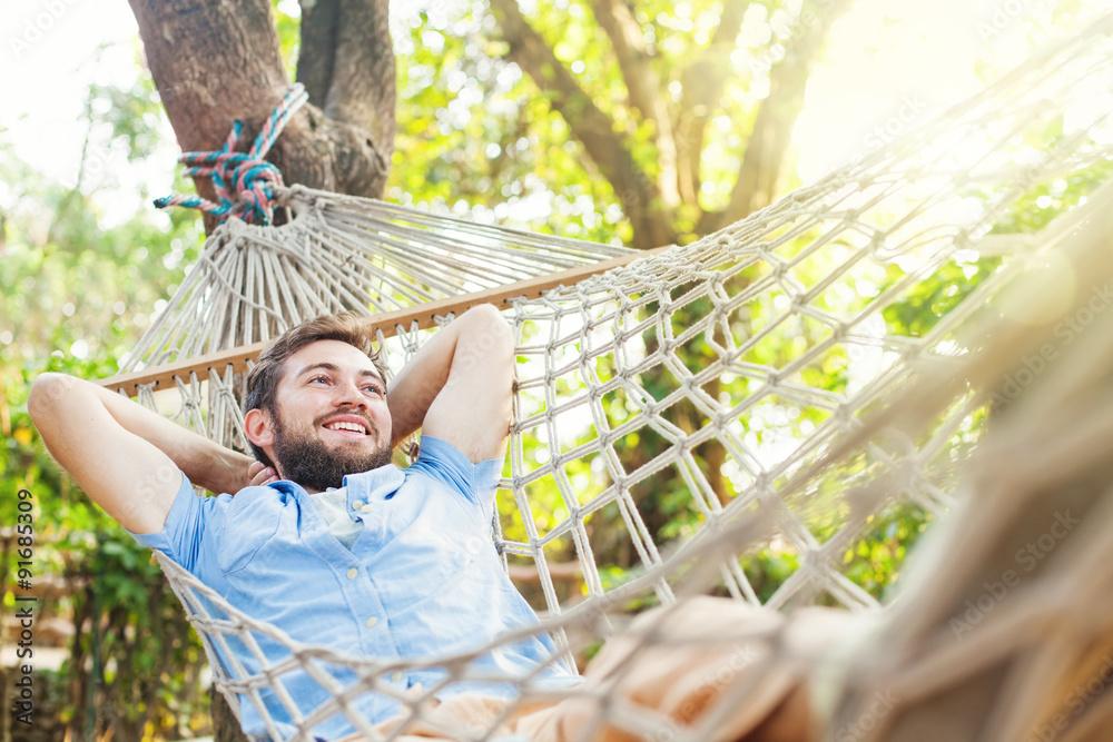 Fototapeta caucasian man using mobile phone white swinging in a hammock