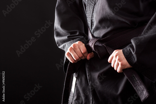 Foto op Aluminium Vechtsport Closeup of male karate fighter tying the knot to his black belt