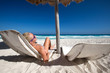Woman relaxing on caribbean beach with sun umbrellas and beds