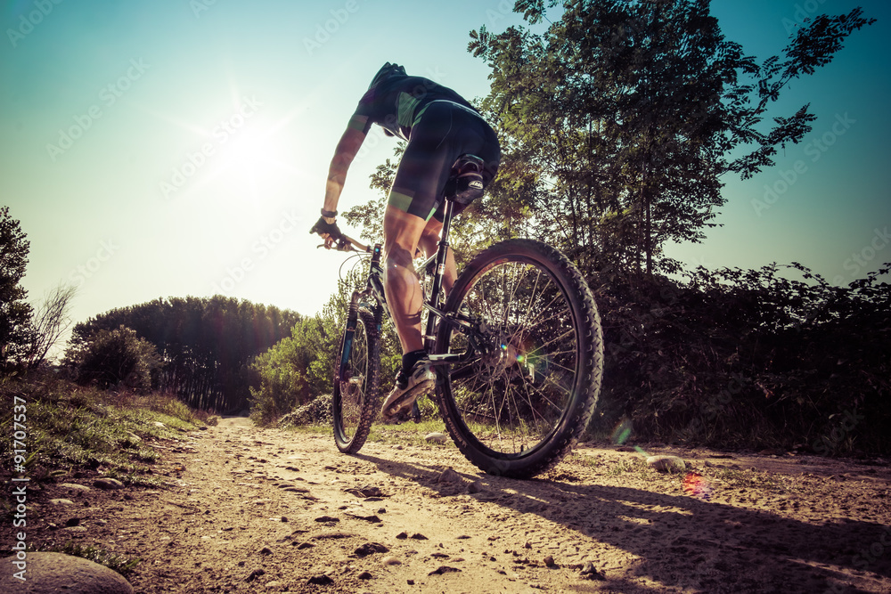Fototapeta Man riding on a dirty road on a mountain bike