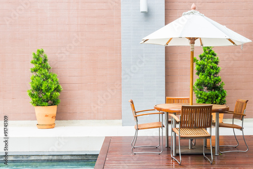 Obraz Table and chair with white umbrella outdoor patio - fototapety do salonu