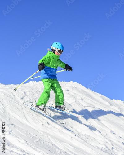 Tuinposter Wintersporten kleiner Junge beim Skifahren