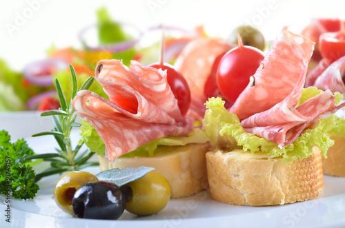 Montage in der Fensternische Bar Partyhäppchen mit feiner italienischer Salami, Salatblatt und Cherrytomate