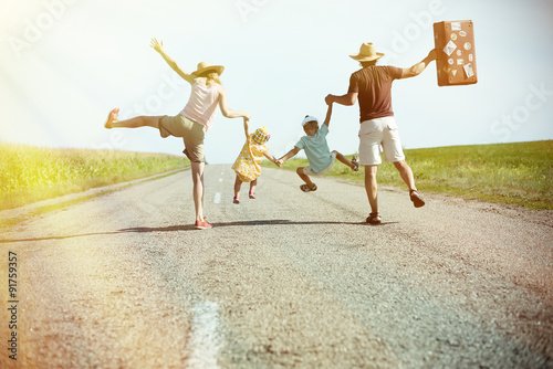 Happy family holding each other hands on sunny country road