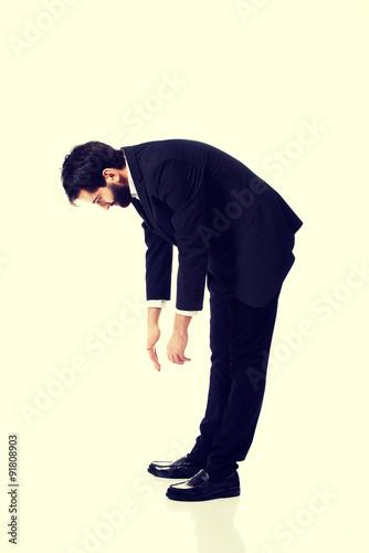 Fotografie, Obraz  Young businessman bending down.