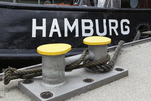 Vászonkép  Aufschrift HAMBURG auf Schiff am Pier, selektive Schärfe