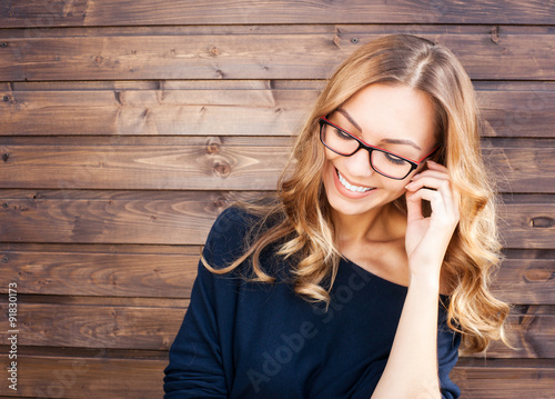 Fotografía  Smiling fashionable blonde laughs outdoors on wooden background