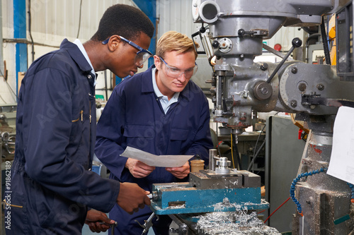 Engineer Showing Apprentice How to Use Drill In Factory Canvas Print