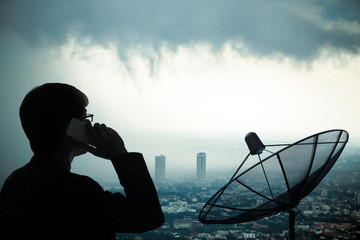 Businessman using smartphone with Satellite dish and strom cloud