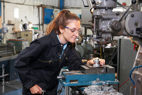 Fotografie, Obraz  Female Apprentice Engineer Working On Drill In Factory