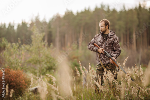 Fotografie, Tablou Young male hunter in camouflage clothes ready to hunt  with hunt