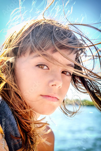 Valokuva  Portrait of a beautiful eight year old girl with the wind blowin
