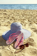 Flip flops and hat on beach sand closeup