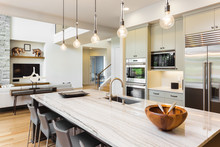 Kitchen In New Luxury Home With Island, Stainless Steel Refrigerator, Microwave, Oven, Pendant Lights, And Chairs