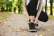 woman goes in for sports, tying shoelace in autumn park