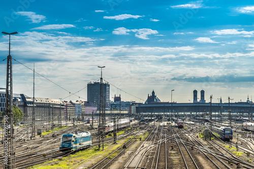 Foto auf AluDibond Bahnhof Gleisanlage am Münchner Hauptbahnhof mit Frauenkirche im Hintergrund