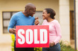 excited black couple holding sold sign