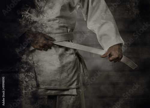 Staande foto Vechtsport Karateka tying the white belt (obi) with grunge background