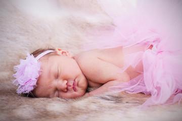 Fototapeta samoprzylepna New born baby wearing a pink head band and tutu.