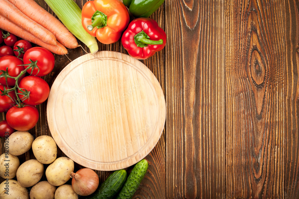 Background of fresh raw vegetables and cutting board