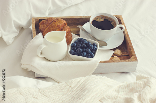 cup of coffee, croissant and fresh blueberry on wooden tray, bre Poster
