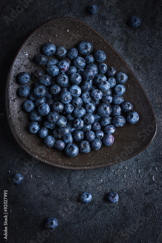Photo  Fresh blueberry on black plate with water drops