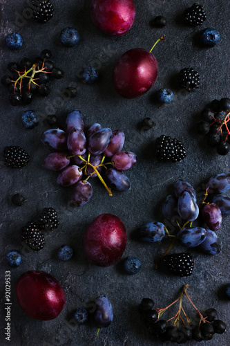 fresh dark fruits and berries on black background. Wallpaper Mural