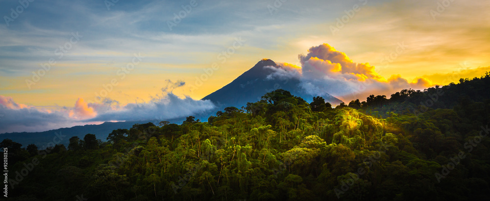 Fototapety, obrazy: Arenal Volcano at Sunrise...A rare sight at the perfect 15 second window to capture sunrise in all of it's glory.  Light glistens off the clouds and the mountain and the jungle.