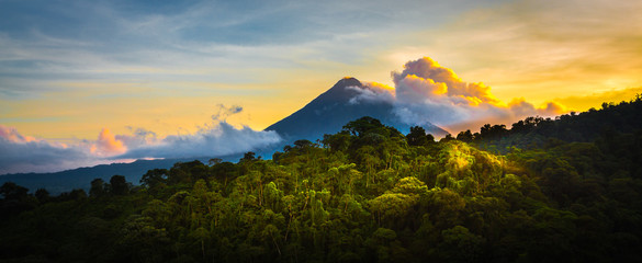 Fototapeta Arenal Volcano at Sunrise...A rare sight at the perfect 15 second window to capture sunrise in all of it's glory. Light glistens off the clouds and the mountain and the jungle.