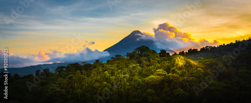 Tuinposter Jungle Arenal Volcano at Sunrise...A rare sight at the perfect 15 second window to capture sunrise in all of it's glory. Light glistens off the clouds and the mountain and the jungle.