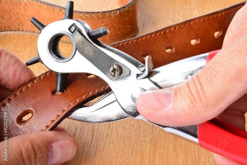 Fotografía Punching holes on leather belt