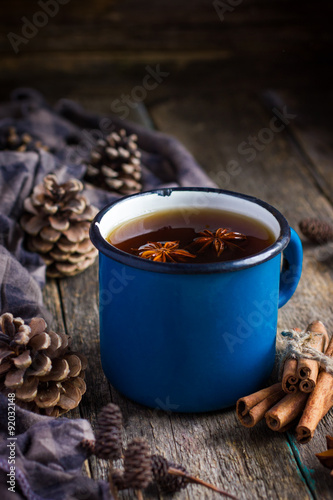 Hot spicy tea with anise and cinnamon in vintage blue enamel mug Poster