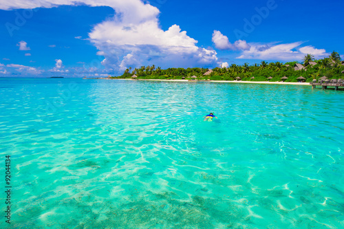 In de dag Groene koraal Young man snorkeling in clear tropical turquoise waters